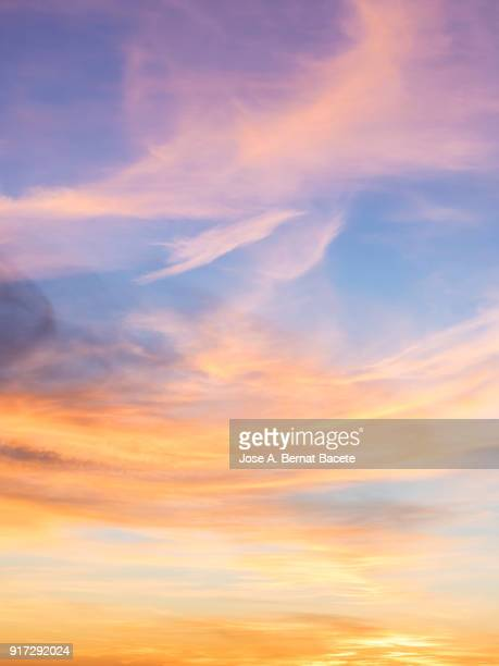 full frame of the low angle view of  sky and clouds of yellow and orange color and the  in the sunset. valencian community, spain - pôr do sol - fotografias e filmes do acervo