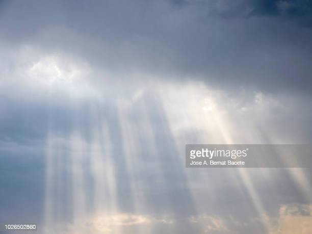 full frame of the low angle view of white and gray clouds of rain and storm with sunbeams. valencian community, spain - zonnestraal stockfoto's en -beelden
