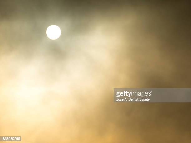 full frame of the sky with the brilliant sun to the dawn with clouds and hazes of colors orange and yellow - heat haze stock pictures, royalty-free photos & images