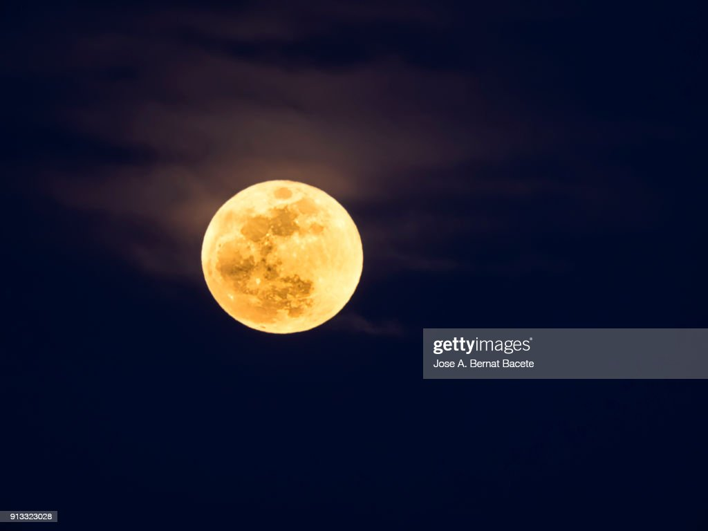 Full frame of the Supermoon of yellow color on a black sky with some high clouds. Valencia, Spain : Stock Photo