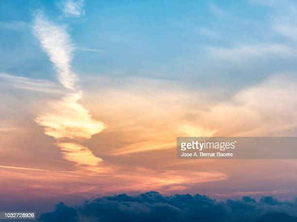 full frame of the surface level view of clouds  and the sun in sky during sunrise. valencian community, spain - alba crepuscolo foto e immagini stock