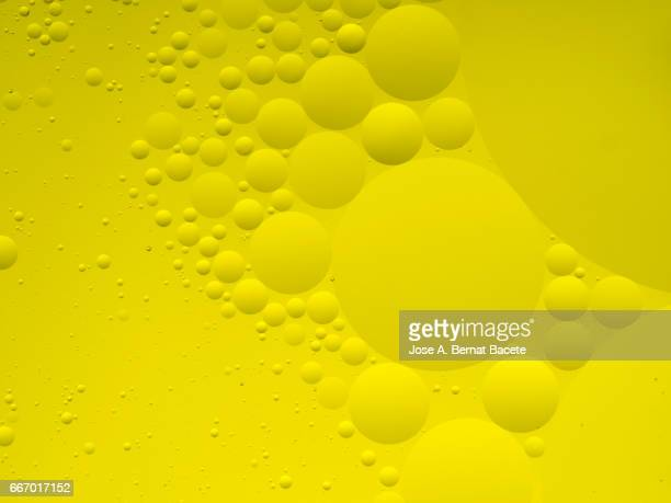Full frame of the textures formed by the bubbles and drops of oil in the shape of circle floating on a yellow colors background