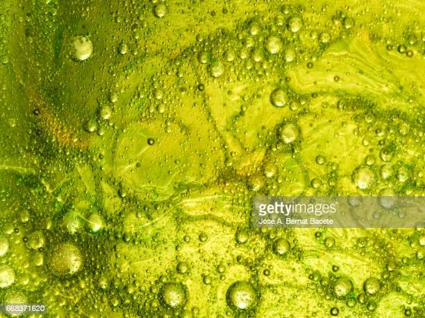 full frame of the textures formed by the bubbles and drops of oil in the shape of circle floating on a gold and green colors background - gota líquido stock pictures, royalty-free photos & images