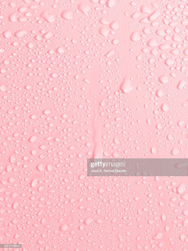 Full frame of the textures formed by the bubbles and drops of water, slipping on the crystal of a window of color pale pink. : Photo