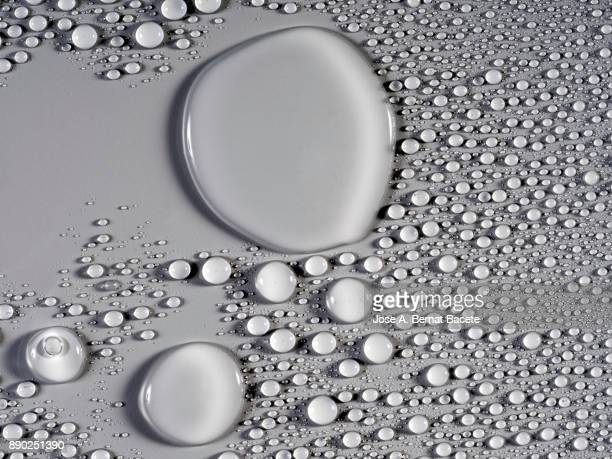 Full frame of the textures formed by the bubbles and drops of water, on a smooth gray background.