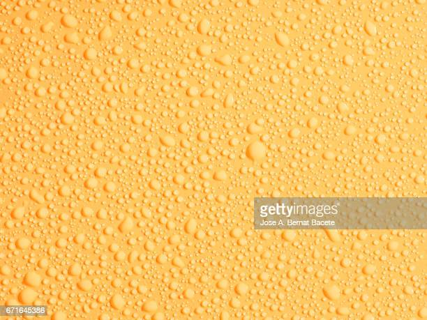Full frame of the textures formed by the bubbles and drops, on a smooth  yellow background
