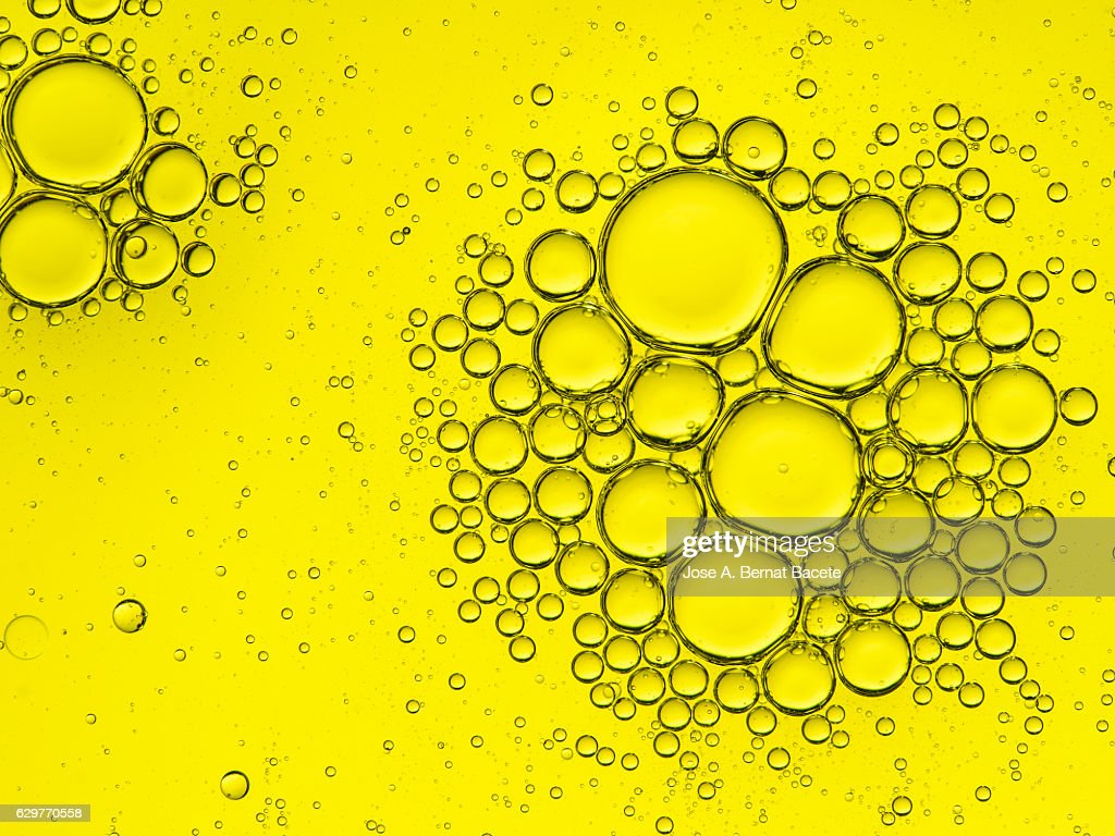 Full frame of the textures formed by the bubbles of oil in the shape of circle floating on the water color yellow : Stock Photo
