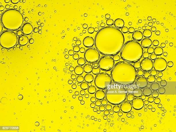 Full frame of the textures formed by the bubbles of oil in the shape of circle floating on the water color yellow