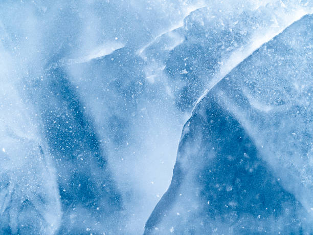 Full frame of the textures formed of a block of cracked ice on a blue color background.