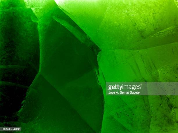 full frame of the textures formed of a block of cracked ice on a green color background. - grüner hintergrund stock-fotos und bilder