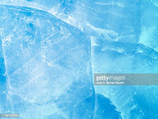 full frame of the textures formed of a block of cracked ice on a light blue color background. - ijs stockfoto's en -beelden