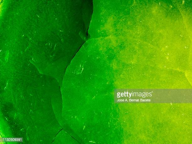 full frame of the textures formed of a block of cracked ice on a green color background. - green background stock pictures, royalty-free photos & images