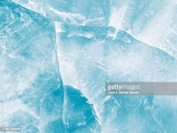 full frame of the textures formed of a block of cracked ice on a soft blue color background. - eis stock-fotos und bilder