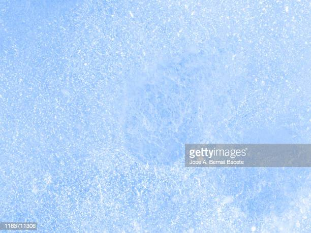 full frame of the textures formed of a block of cracked ice on a soft blue color background. - frost stock pictures, royalty-free photos & images