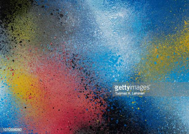 full frame photo of a colorful and splattered spray paint background. - graffiti foto e immagini stock