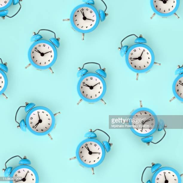 full frame shot of alarm clocks on table - wall clock stock photos and pictures