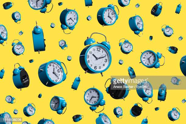 full frame shot of alarm clocks on yellow background - día fotografías e imágenes de stock