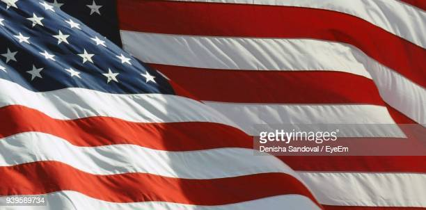 full frame shot of american flag waving during sunny day - stars and stripes stock pictures, royalty-free photos & images
