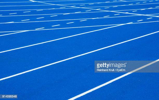 full frame shot of blue running track - track and field stadium stock pictures, royalty-free photos & images
