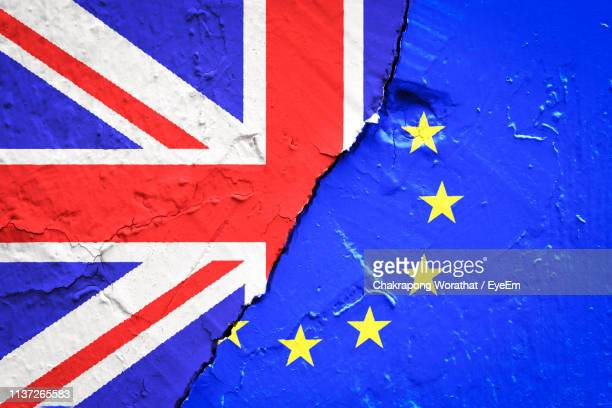 full frame shot of british and european union flags on cracked wall - brexit stock pictures, royalty-free photos & images