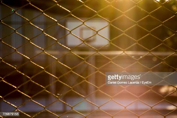 Full Frame Shot Of Chainlink Fence Against Basketball Hoop During Sunset