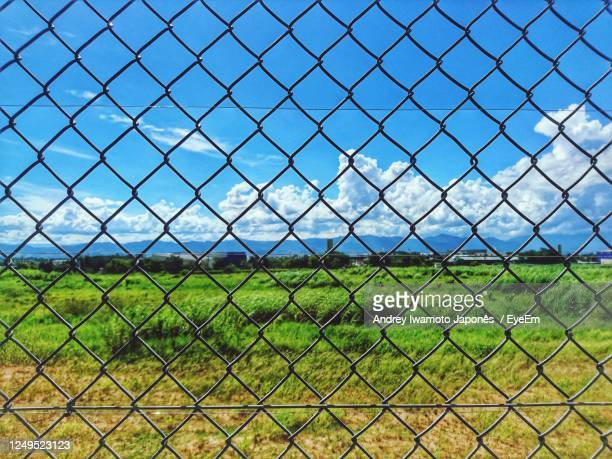full frame shot of chainlink fence against blue sky - japonês stock pictures, royalty-free photos & images