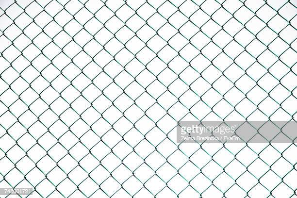 full frame shot of chainlink fence against sky - hek stockfoto's en -beelden