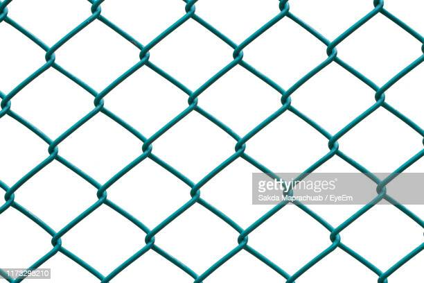 full frame shot of chainlink fence against white background - chainlink fence stock pictures, royalty-free photos & images
