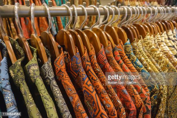 full frame shot of clothes hanging on rack for sale in store - essentials collection stock pictures, royalty-free photos & images