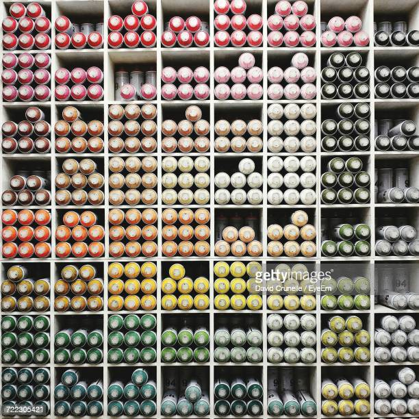 Full Frame Shot Of Colorful Spray Cans Arranged On Shelves At Store For Sale