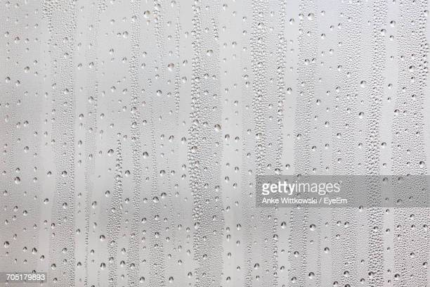 Full Frame Shot Of Condensed Window Glass During Rain