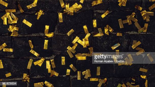 full frame shot of confetti on footpath - gold confetti stock photos and pictures