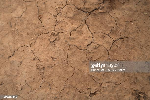 full frame shot of cracked land - brown stock pictures, royalty-free photos & images