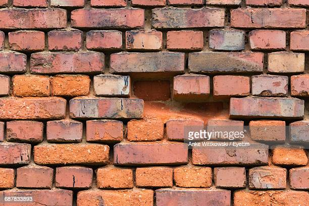 full frame shot of damaged brick wall - incomplete stock pictures, royalty-free photos & images