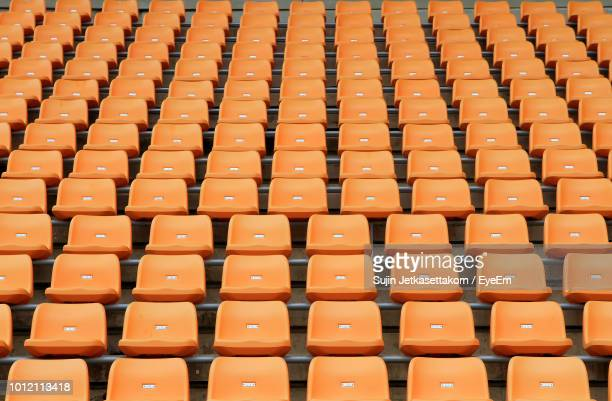 full frame shot of empty orange chairs - empty bleachers stockfoto's en -beelden