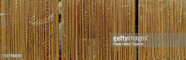 full frame shot of gold chains hanging in store - gold chain necklace stock pictures, royalty-free photos & images