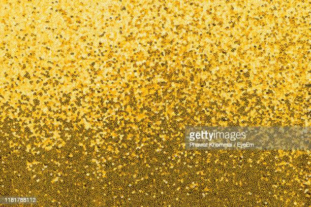 full frame shot of gold colored sequins - sequin stock pictures, royalty-free photos & images