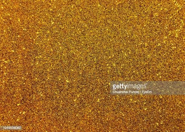 full frame shot of golden shimmer - glittering stock pictures, royalty-free photos & images
