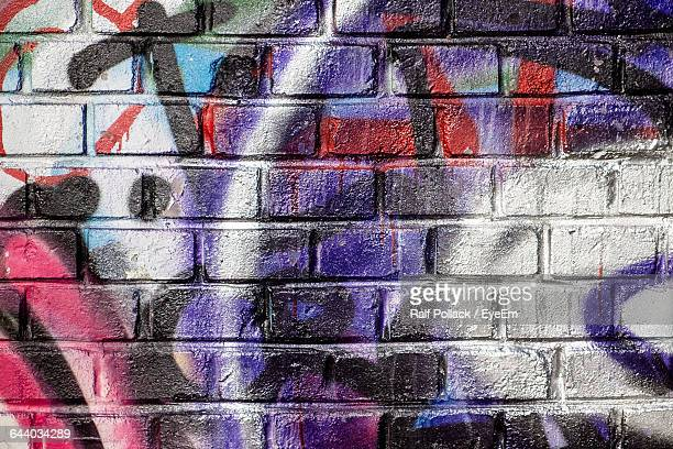 full frame shot of graffiti on brick wall - graffiti stock pictures, royalty-free photos & images