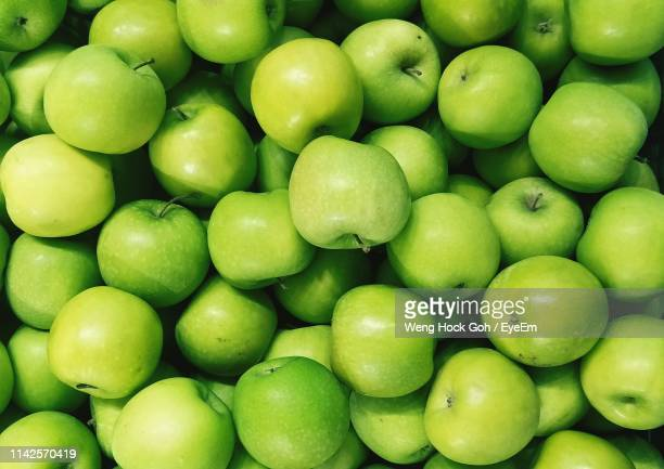 full frame shot of granny smith apples for sale in market - りんご ストックフォトと画像