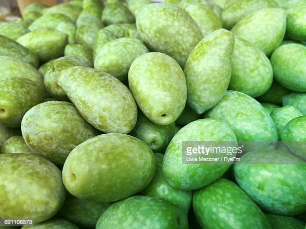 full frame shot of green olives for sale at market stall - green olive stock photos and pictures
