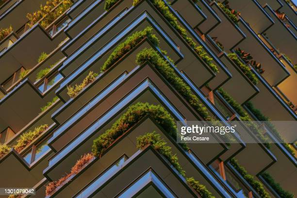full frame shot of green plants in the balconies of a high riser building. - sustainable resources stock pictures, royalty-free photos & images