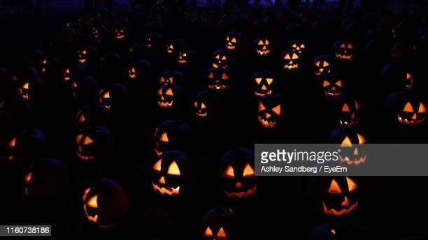full frame shot of illuminated jack o lanterns at night - happy halloween stock photos and pictures