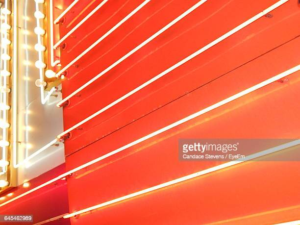 Full Frame Shot Of Illuminated Neon Lights Against Orange Wall