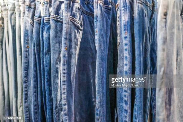 full frame shot of jeans hanging at store - denim stock pictures, royalty-free photos & images
