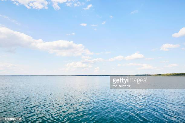 full frame shot of lake, clouds and blue sky, backgrounds - meer stock-fotos und bilder
