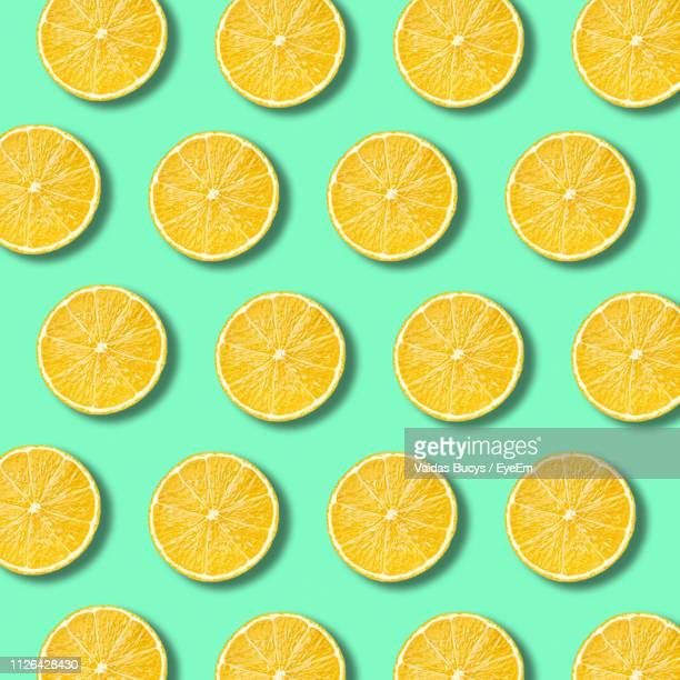 full frame shot of lemon slices over turquoise background - educational subject stock pictures, royalty-free photos & images