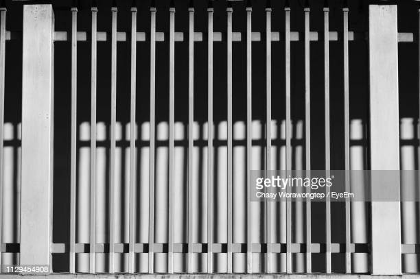 full frame shot of metal fence against building - prison bars stock pictures, royalty-free photos & images