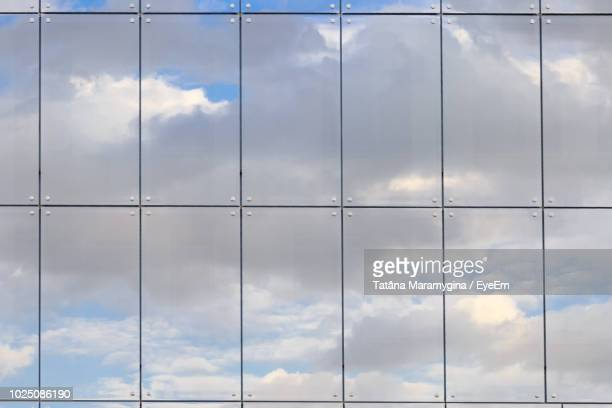 full frame shot of modern glass building with clouds reflection - fensterfront stock-fotos und bilder