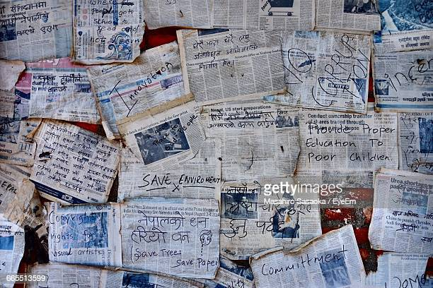 full frame shot of old newspaper stuck on wall - western script stock pictures, royalty-free photos & images